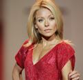 Talk show host Kelly Ripa walks the runway in a designer red dress