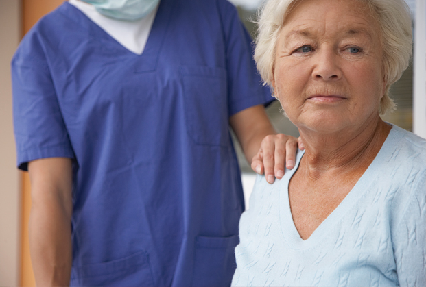 Elderly female patient with health care provider's hand on shoulder