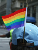 Photograph of a person wearing a baseball cap with a rainbow flag in it.