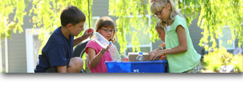 Four young children organizing recyclables
