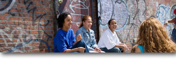 A group of youth sitting in front of a graffitied wall