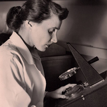 photo of Dr. Ruth Kirschstein looking into a microscope.