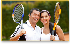 Una pareja sonríe mientras sostienen sus raquetas de tenis
