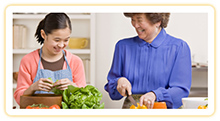 A grandmother and granddaughter having fun making dinner