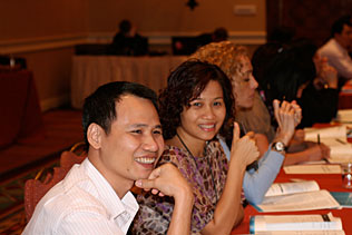 Thai N. Hoang, Vietnam and Minh Huong, Vietnam, smiling while sitting and listening during the plenary session.