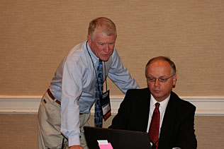Mike Walsh, The Walsh Group and Alain Verstraete, Belgium looking at a laptop screen.