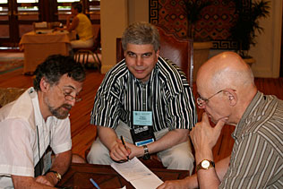 Jeff Samet, Boston University; Evgeny Krupitsky, Russia; and Edwin Zvartau, Russia sitting around a table discussing notes.