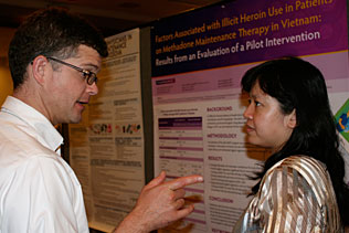 Alex Walley, Univ of Boston and Nhu To Nguyen, Vietnam speaking to each other in front of Dr. Nguyens poster presentation.