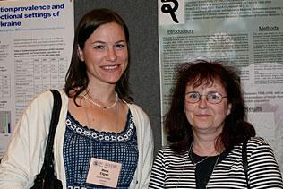 Maria Ellgren, AstraZeneca, Sweden and Eva Keller, Hungary standing together and smiling in front of poster presentations.