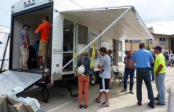 Estos residentes de Dakota Dunes evacuados se forman frente al remolque del puesto de comando de información sobre incidentes