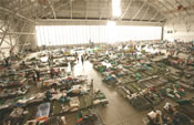 Cots and people inside a large airplane hangar