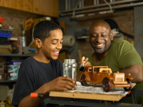 A photo of an African American mentor and a boy woodworking.