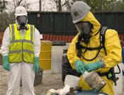 Un especialista ambiental desecha cuidadosamente de químicos derramados por el huracán Rita