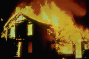 House engulfed in fire against night sky