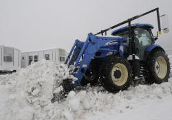 Heavy snow is cleared with a tractor from the Temporary Housing Unit staging area