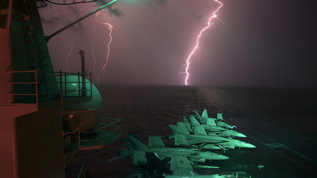 Image description: Flashes of lightning are seen over the horizon as the aircraft carrier USS Dwight D. Eisenhower operates in the Persian Gulf area. Photo by Lt. Greg Linderman, U.S. Navy.