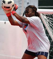 Photograph of a young goalie intercepting a soccer ball.