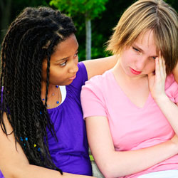 Photograph of a teen girl comforting another, unhappy, teen girl.