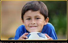 Un niño está acostado boca abajo sosteniendo un balón