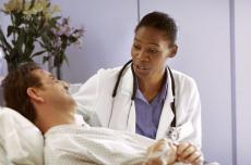 Photograph of a female doctor talking to a male patient in a hospital bed