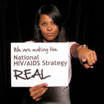 Woman holding sign 'Facing AIDS by making the National HIV/AIDS Strategy REAL.'