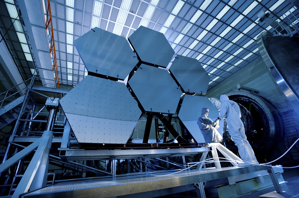 Image description: Ball Aerospace's Jake Lewis is reflected in one of the mirrors on a James Webb Space Telescope. Photo by David Higginbotham and Emmett Given, NASA.