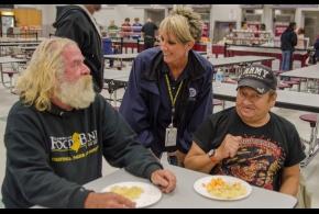 Sandy Hendrix, miembro de los Equipos de Relaciones con la Comunidad de FEMA conversa con sobrevivientes Tom Weinstein y Joey Perez en un albergue de la Cruz Roja Americana en la Escuela Superior Pleasantville.