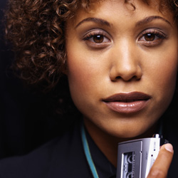Photograph of a young woman holding a tape recorder.
