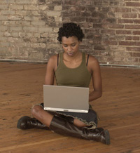 Photograph of a young woman using a laptop computer for research.