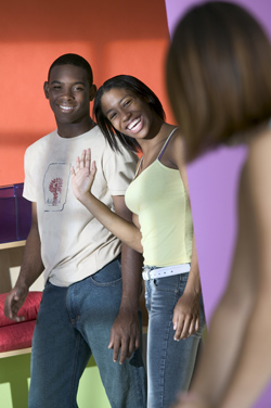 Two young people are welcomed into a room by another young person.