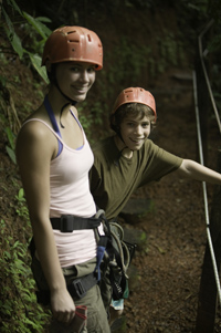 Two young people preparing for rock climbing.