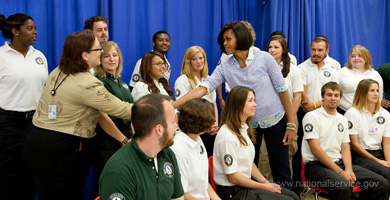 Photograph of First Lady Michelle Obama shaking the hand of an Americorps leader, in a group of corps members.  Photograph courtesy of the Corporation for National and Community Service.