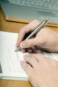Photograph of a hand using a pencil to fill out a form.