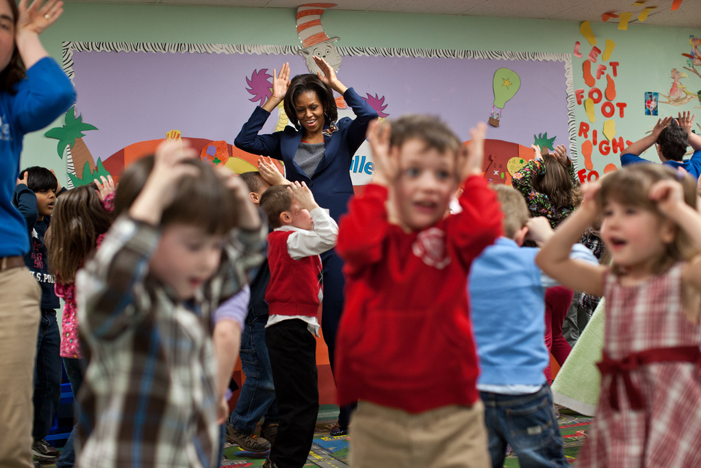 "Image description: First Lady Michelle Obama participates in the ""Bunny Pokey"" song and dance with kids in the Kinderbees Activty Room at Penacook Community Center in Penacook, NH on March 9, 2012. Photo by Lawrence Jackson, White House"