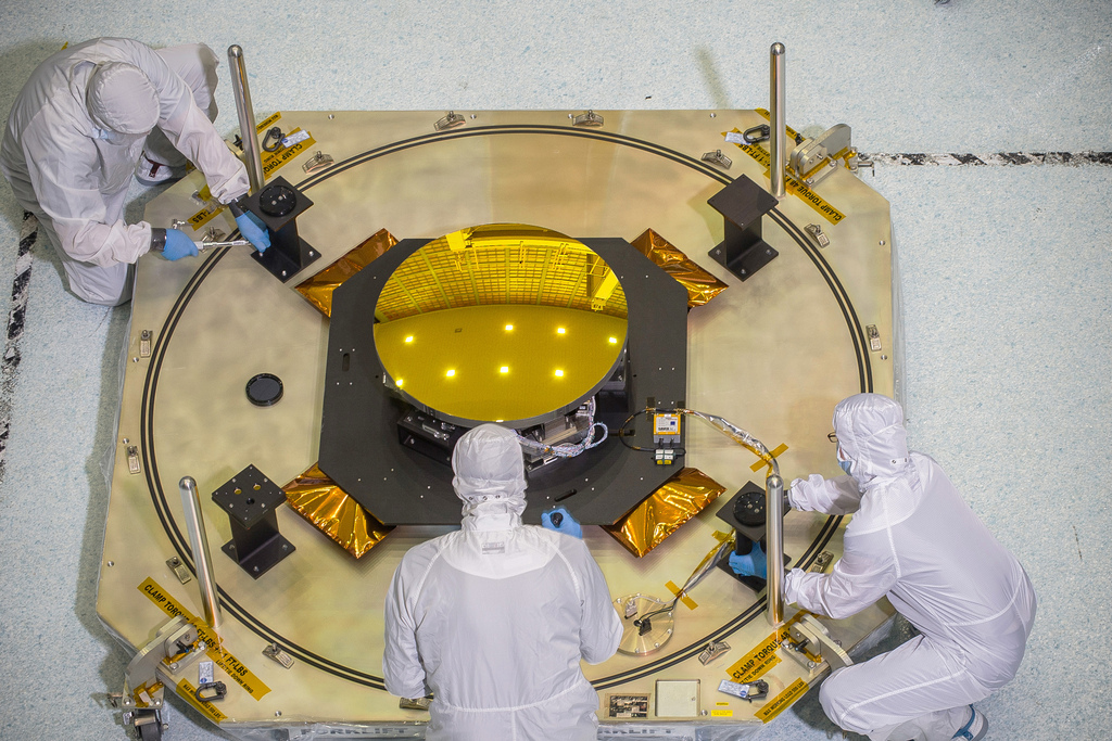 Image description: This round, gold coated secondary mirror that looks like a sun will fly aboard NASA's James Webb Space Telescope. The thickness of the gold coating on the mirrors is only 100 nanometers thick. A human hair is roughly 1,000 times thicker. Photo by Chris Gunn, NASA.