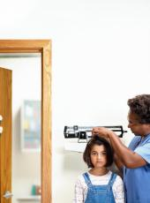 Photograph of a female nurse measuring a young girl's height