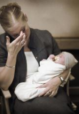 Photograph of a woman, looking upset, holding a baby