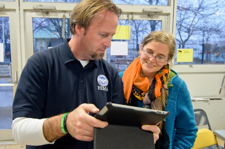 Disability Integration Advisor demonstrates iPad with accessibility features to disaster recovery center worker.