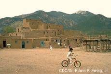 Photograh of a Native American boy riding a bicycle at Taos Pueblo, Taos, New Mexico