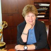 A woman sitting at a desk, next to an academy award.