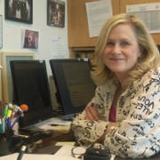 NIDA Communications Director, Carol Krause, sitting at her desk