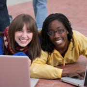 Two girls on their laptops.