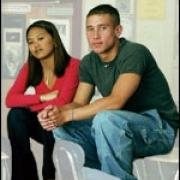 Two teens sitting on a desk at school