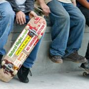 Three teens sitting and one is holding a skateboard