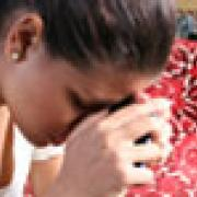 girl with her hand on her forehead showing she is upset and sad