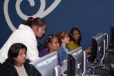 Four women learn computer basics from a Youth Policy instructor