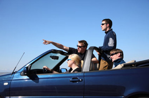 Photo shows an adolescent girl driving a convertible with three other adolescents as passengers—one has his right arm extended above the windshield, pointing at something in the distance, and another is standing in the back.