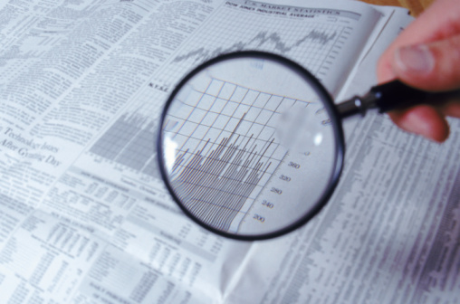 Magnifying glass and financial charts