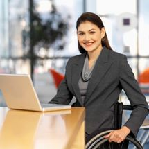 A woman in a wheelchair works on a laptop