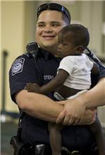 A U.S. Customs and Border Protection officer waits in the processing area with one of the orphans arriving from Haiti in Sanford, FL.